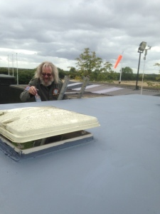 Jonty hard at work giving the caravan roof a water-tight coating