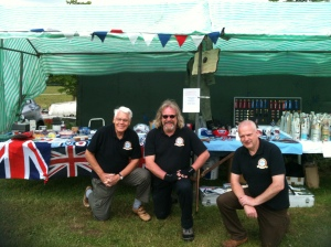 Ralph, Jonty and Paul photographed in front of the Tombola and Wine or Water stalls on the Sunday